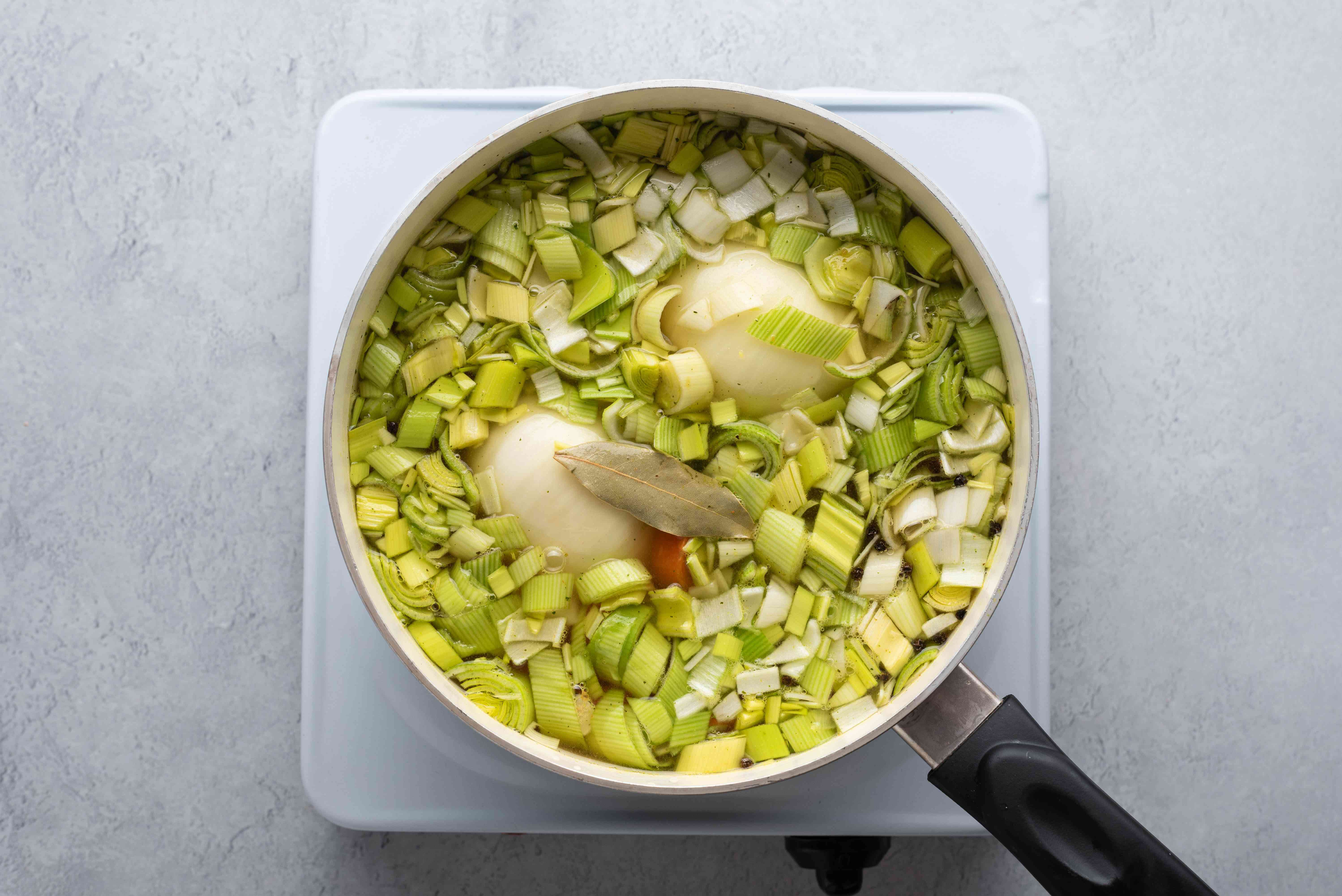 Add the leeks, carrots, celeriac, bay leaf, peppercorns, and broth to the onion in the saucepan
