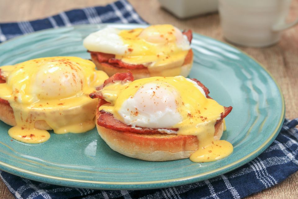 Homemade hollandaise sauce over eggs Benedict