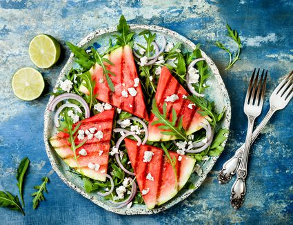 Grilled watermelon salad with feta cheese, arugula, onions on blue background