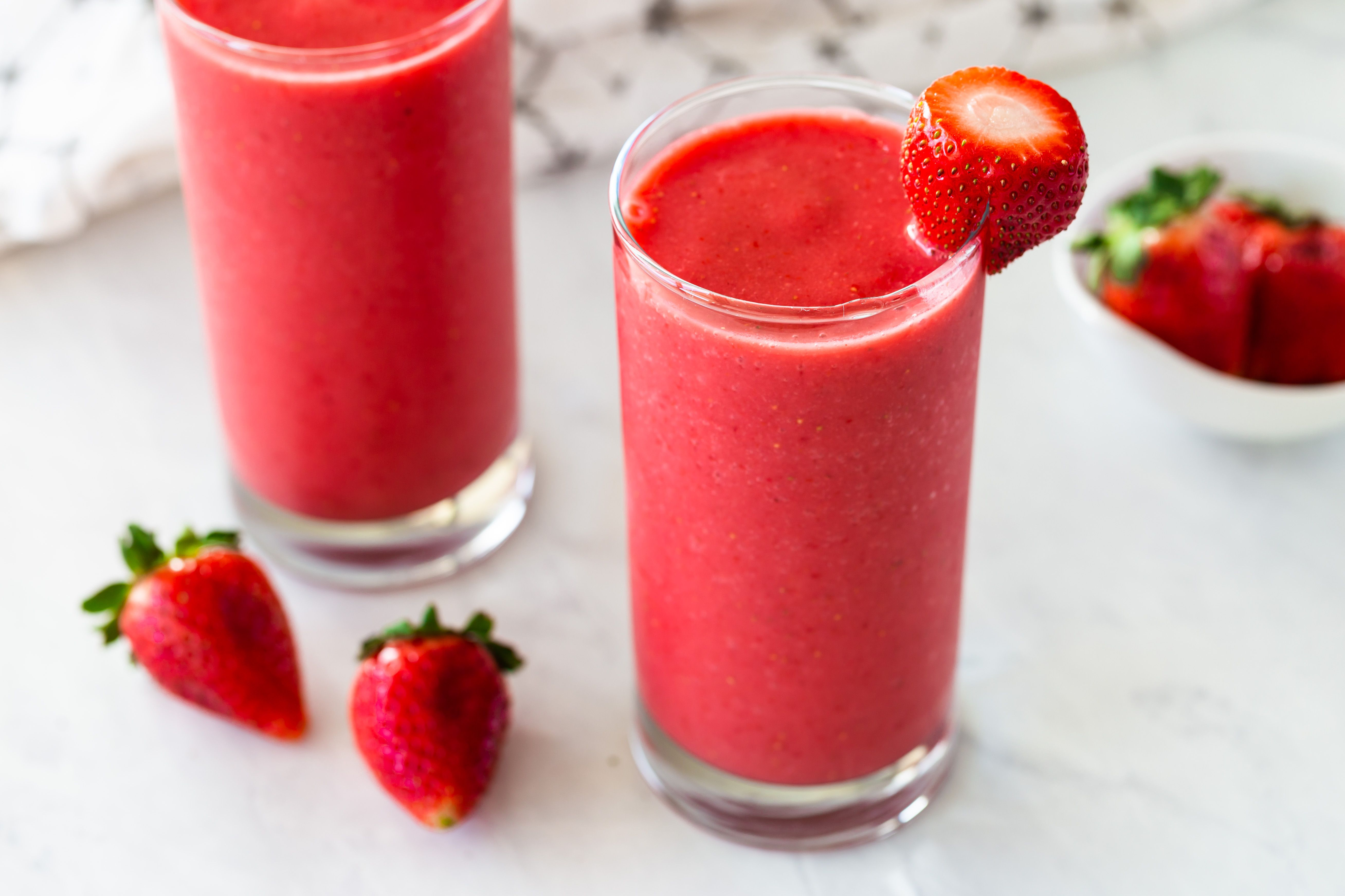 Strawberry smoothies in two glasses garnished with strawberries