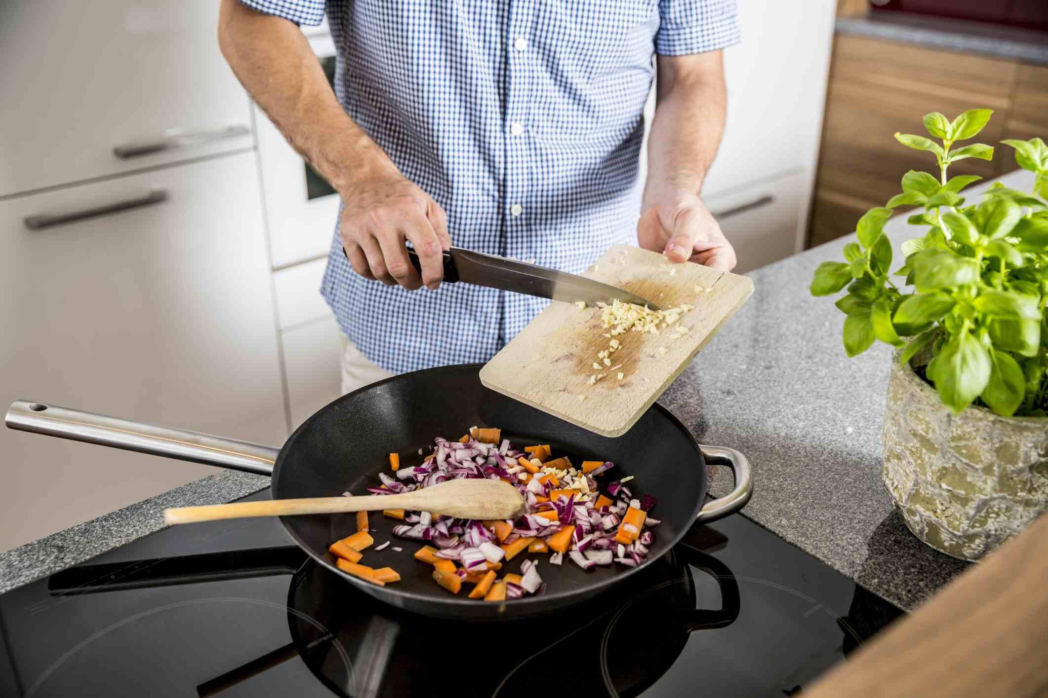 Man putting garlic into nonstick pan