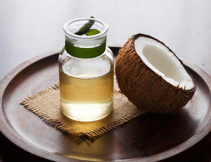 Coconut oil and half a coconut on a wooden tray.