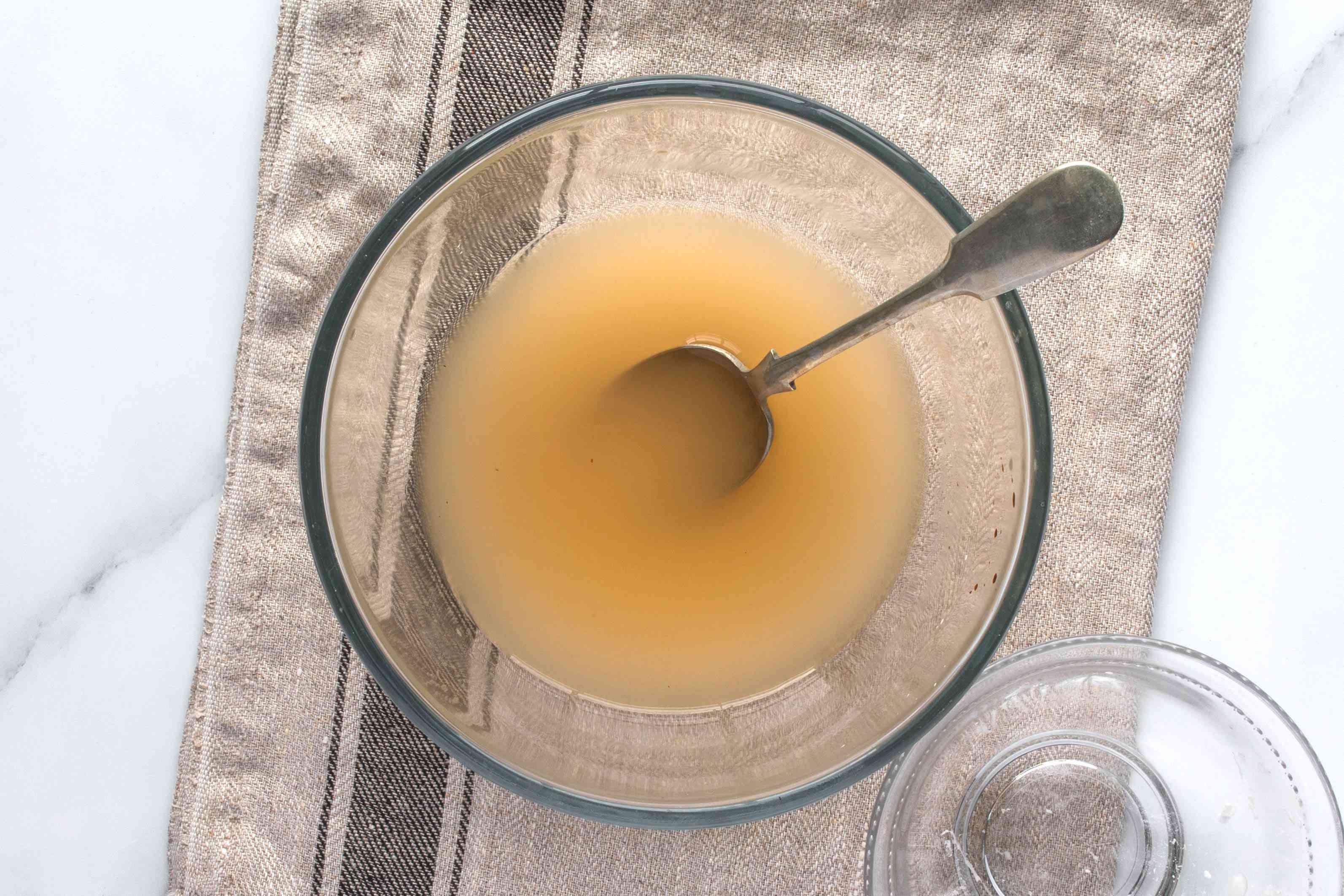 Potato starch mixed into shiitake soaking liquid in a bowl
