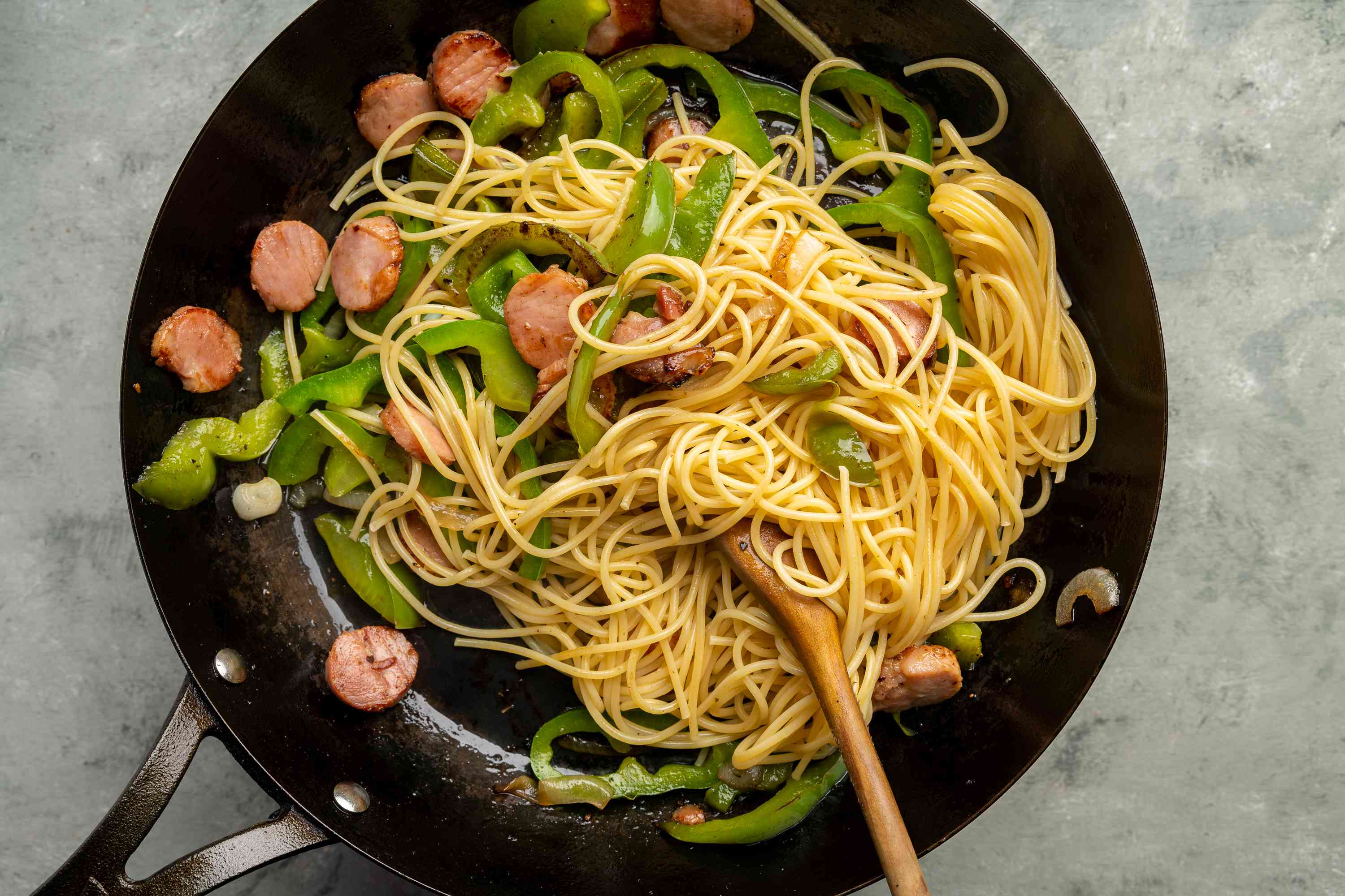 spaghetti added to the pepper and sausage in the skillet