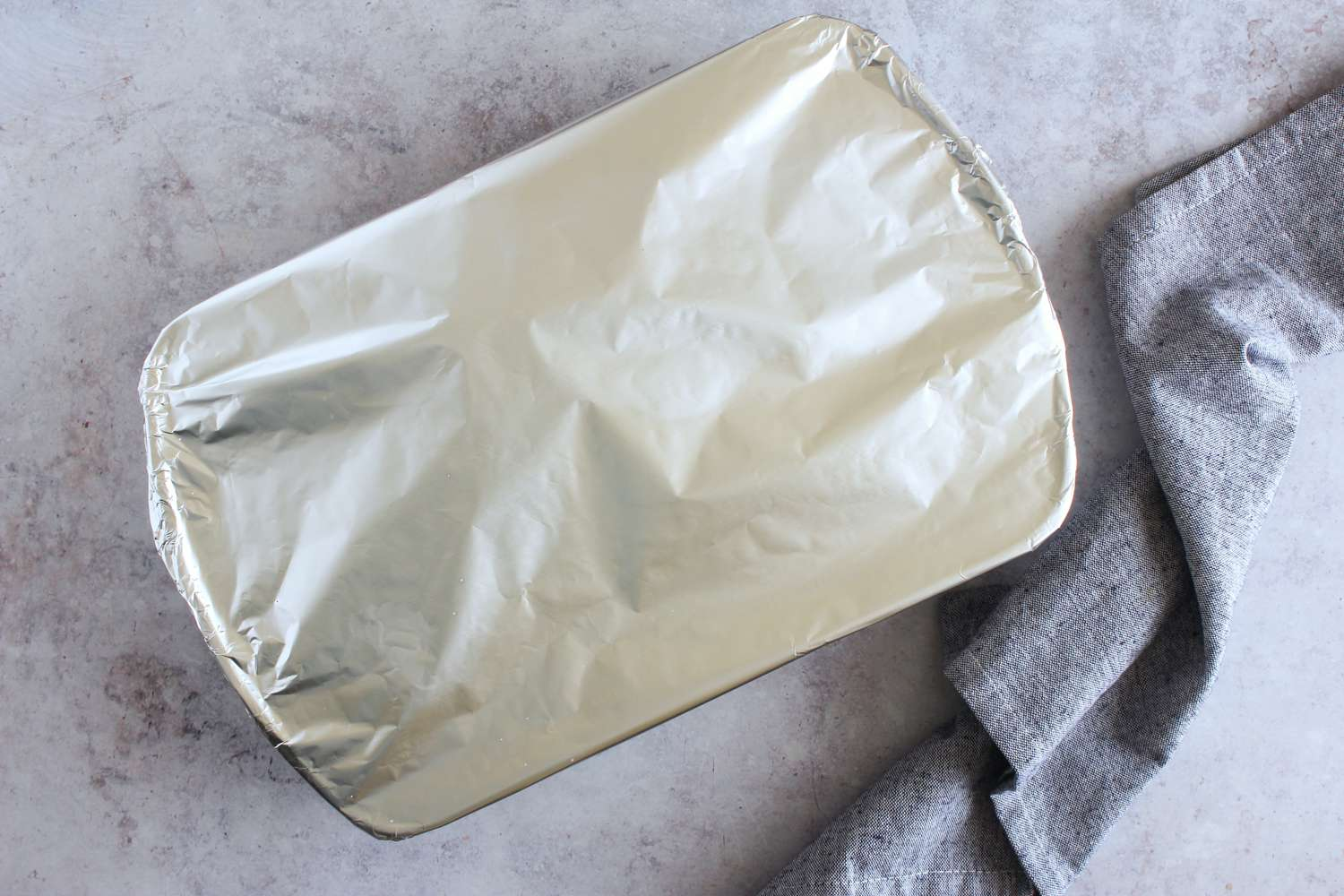 Salted chicken breasts in a dish covered with aluminum foil
