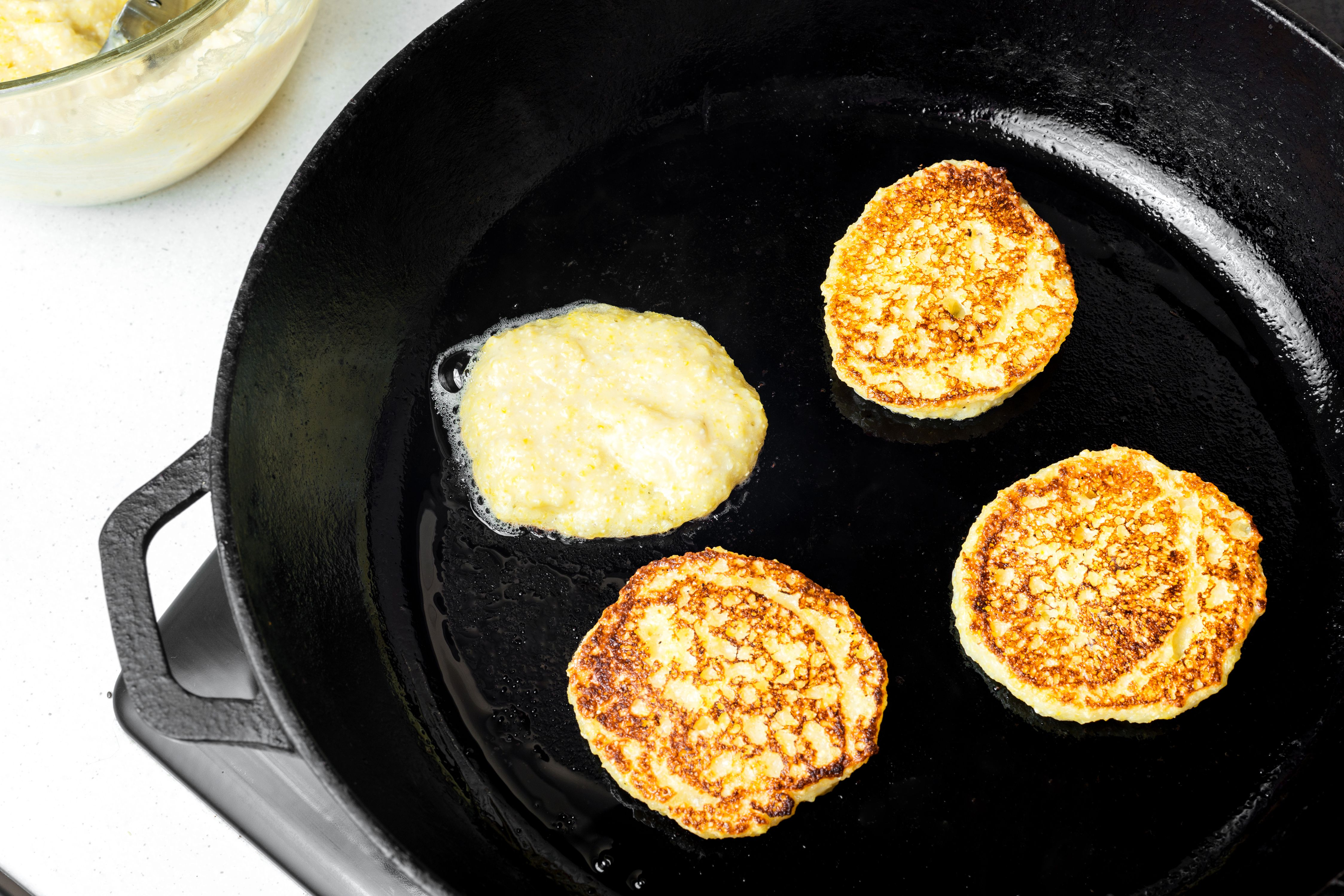 Johnnycakes being cooked on a skillet