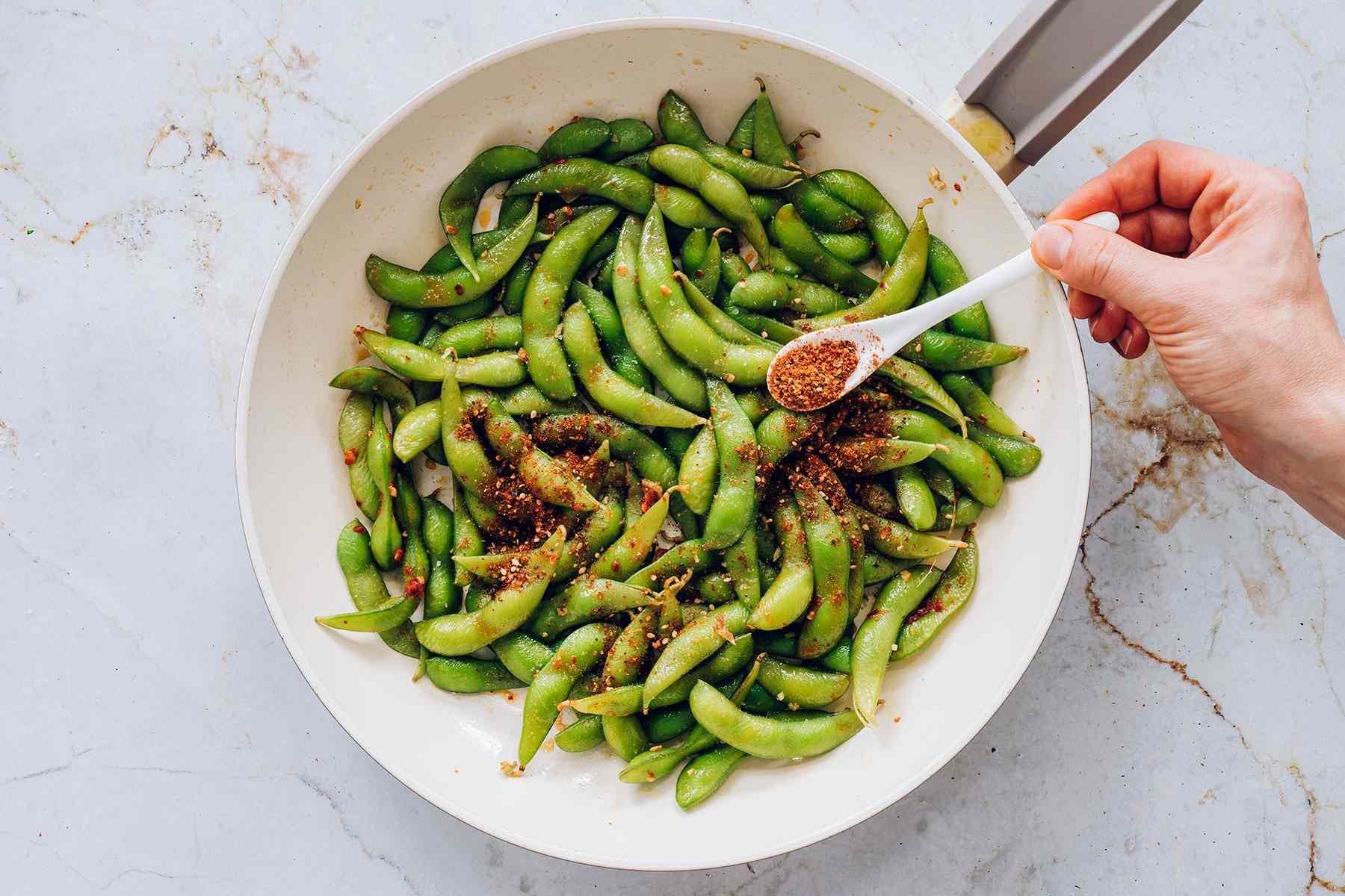 Add shichimi togarashi to the edamame mixture in the pan