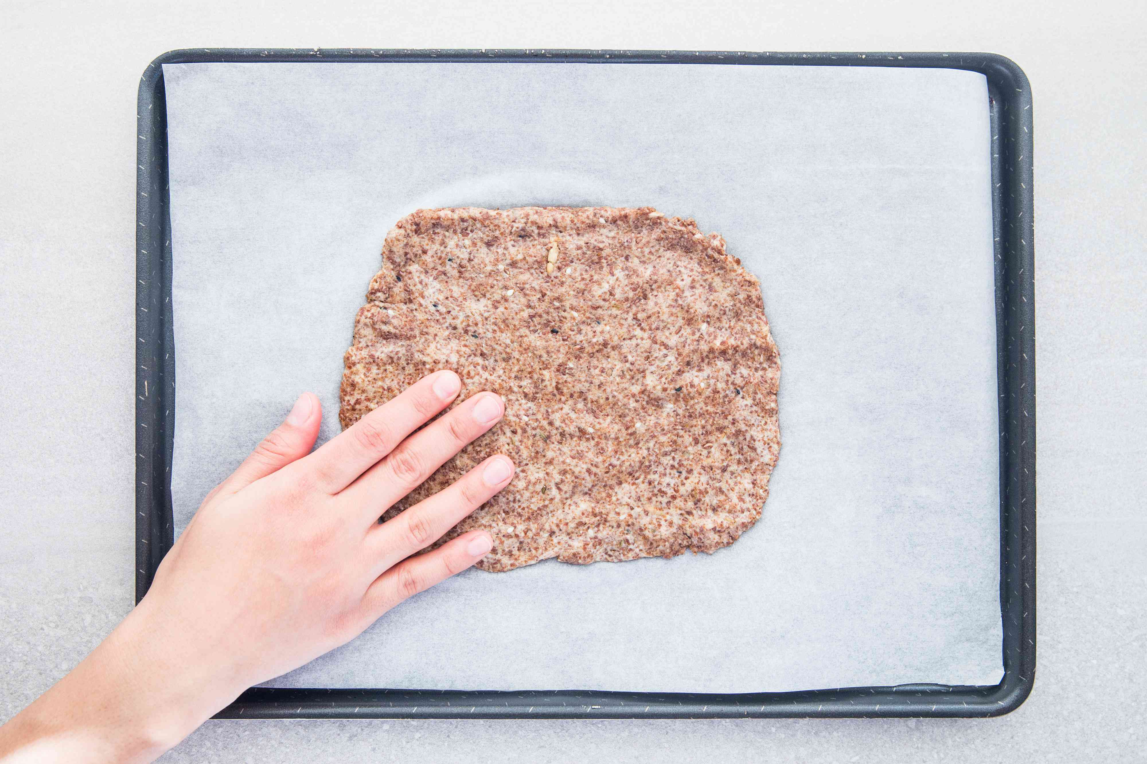 Cracker dough on a baking sheet lined with a parchment paper