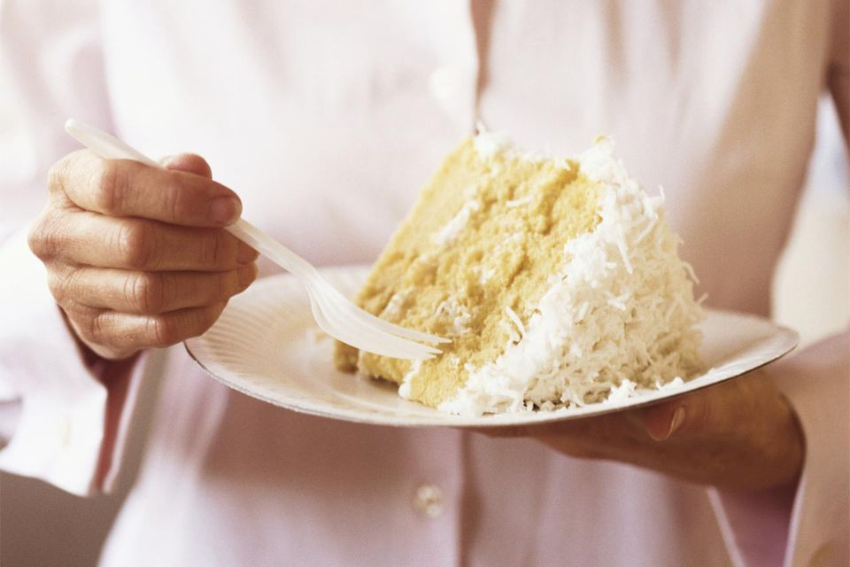 Woman holding a piece of coconut cake on paper plate