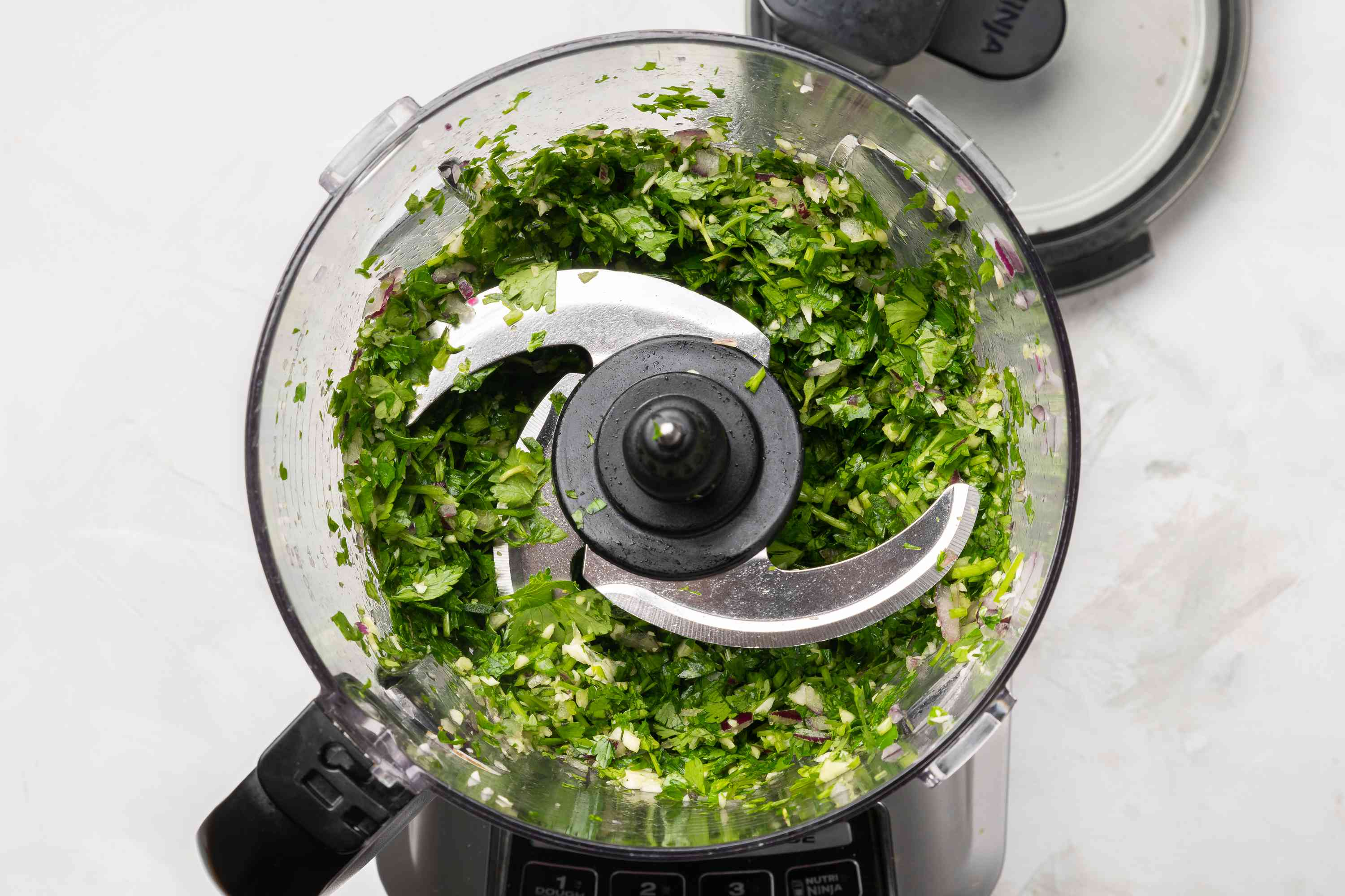 Add the parsley, oregano, and cilantro to the onions and garlic in the food processor