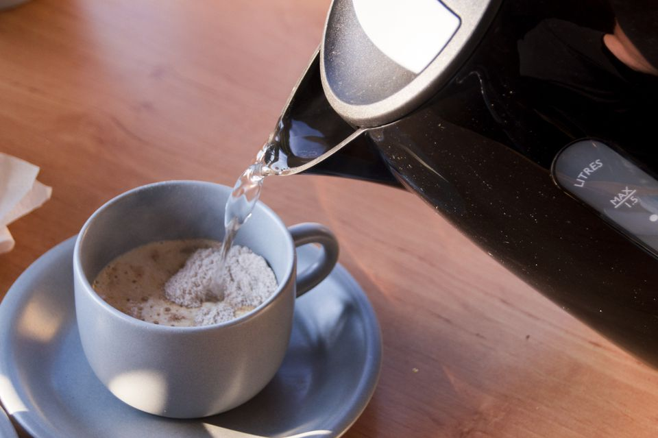 pouring hot water in grey cup with instant coffee against wooden background