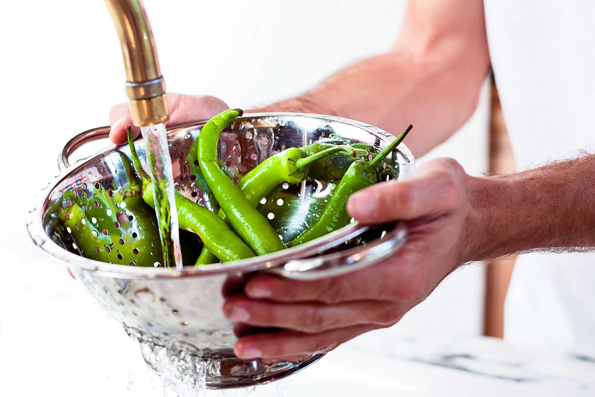 Person washing chiles in colander.