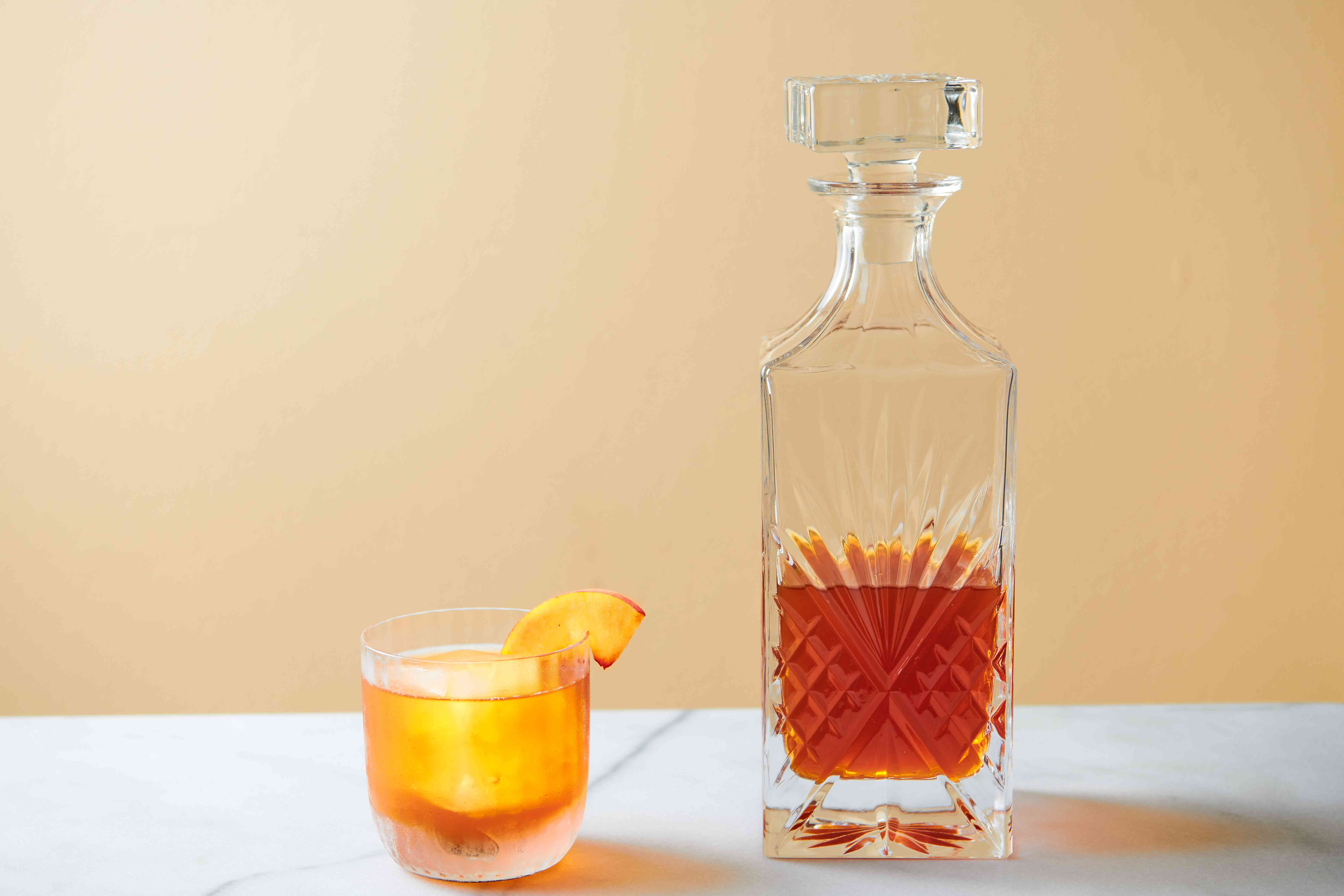 A glass of peach liqueur with ice and a decanter filled with peach liqueur