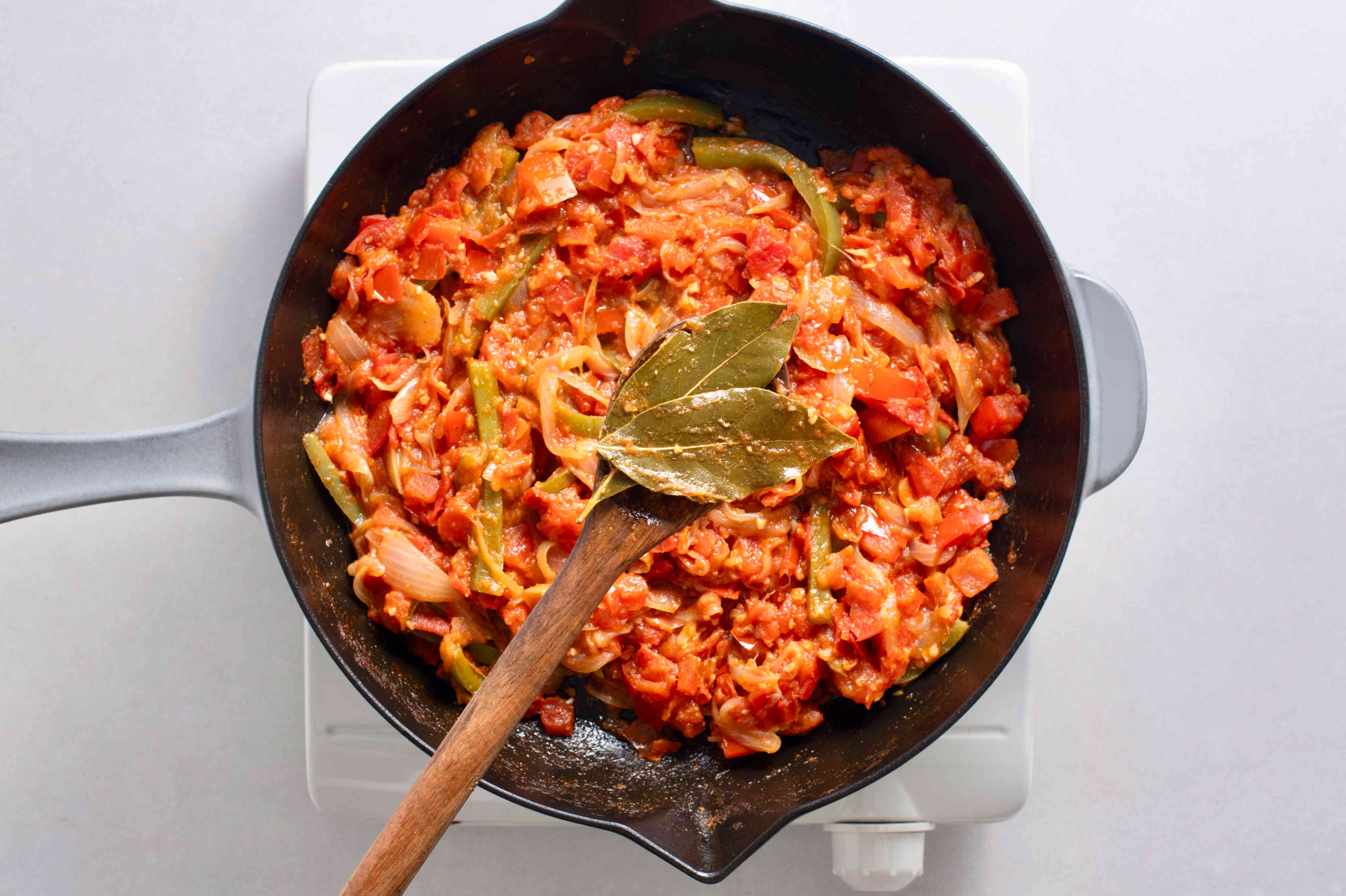 remove the bay leaves from the vegetable mixture in the skillet