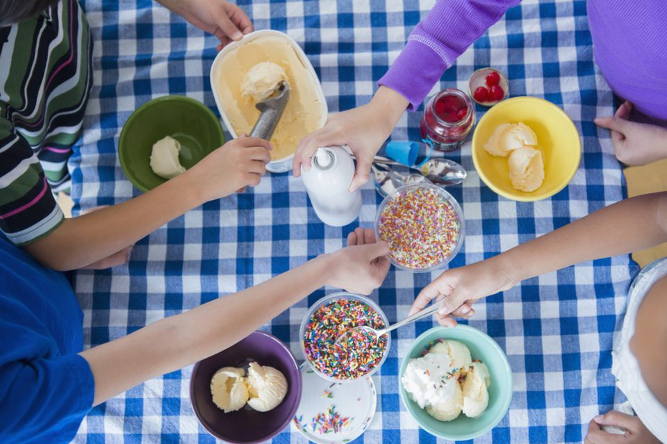 Hands making ice cream sundaes on a blue-and-white checkered tablecloth