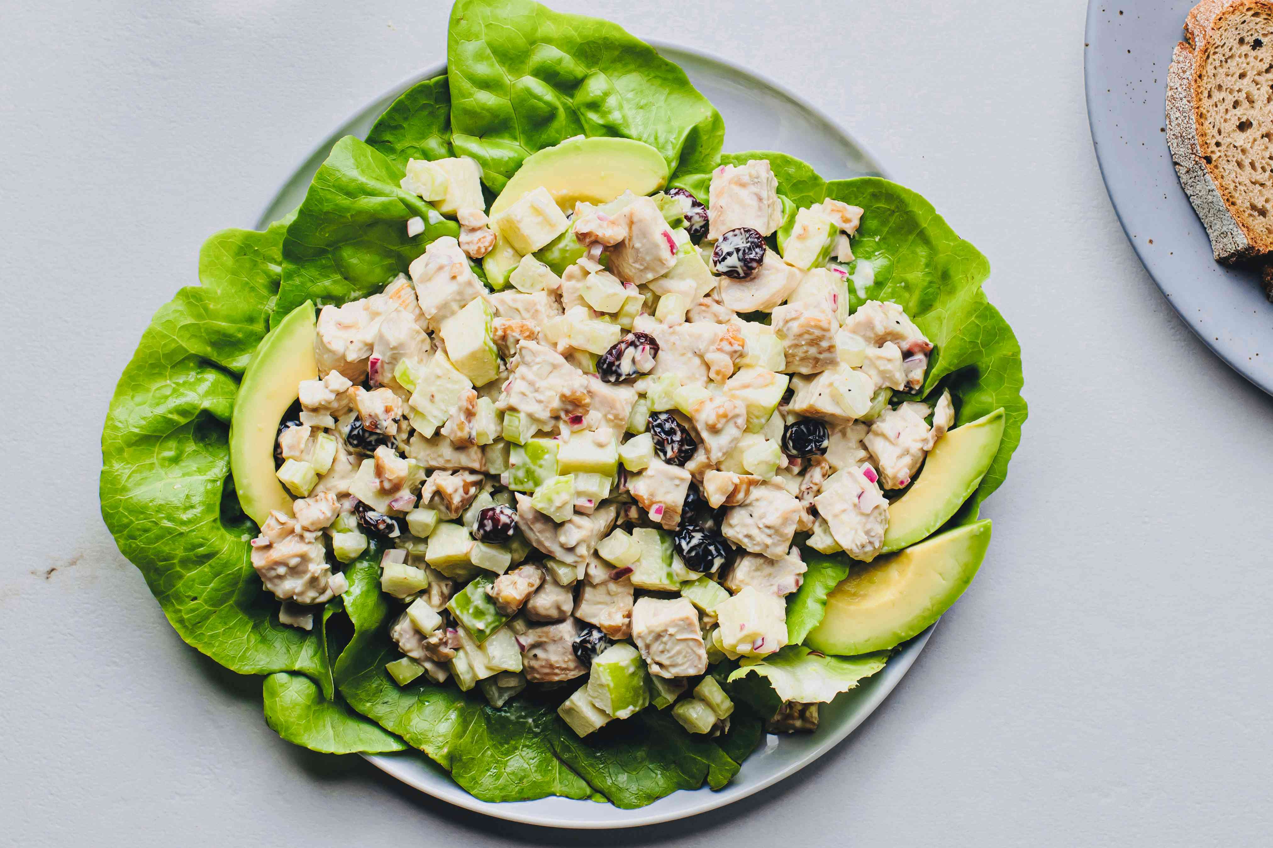 Chicken salad with apples and cranberries in a bowl, with lettuce and avocados