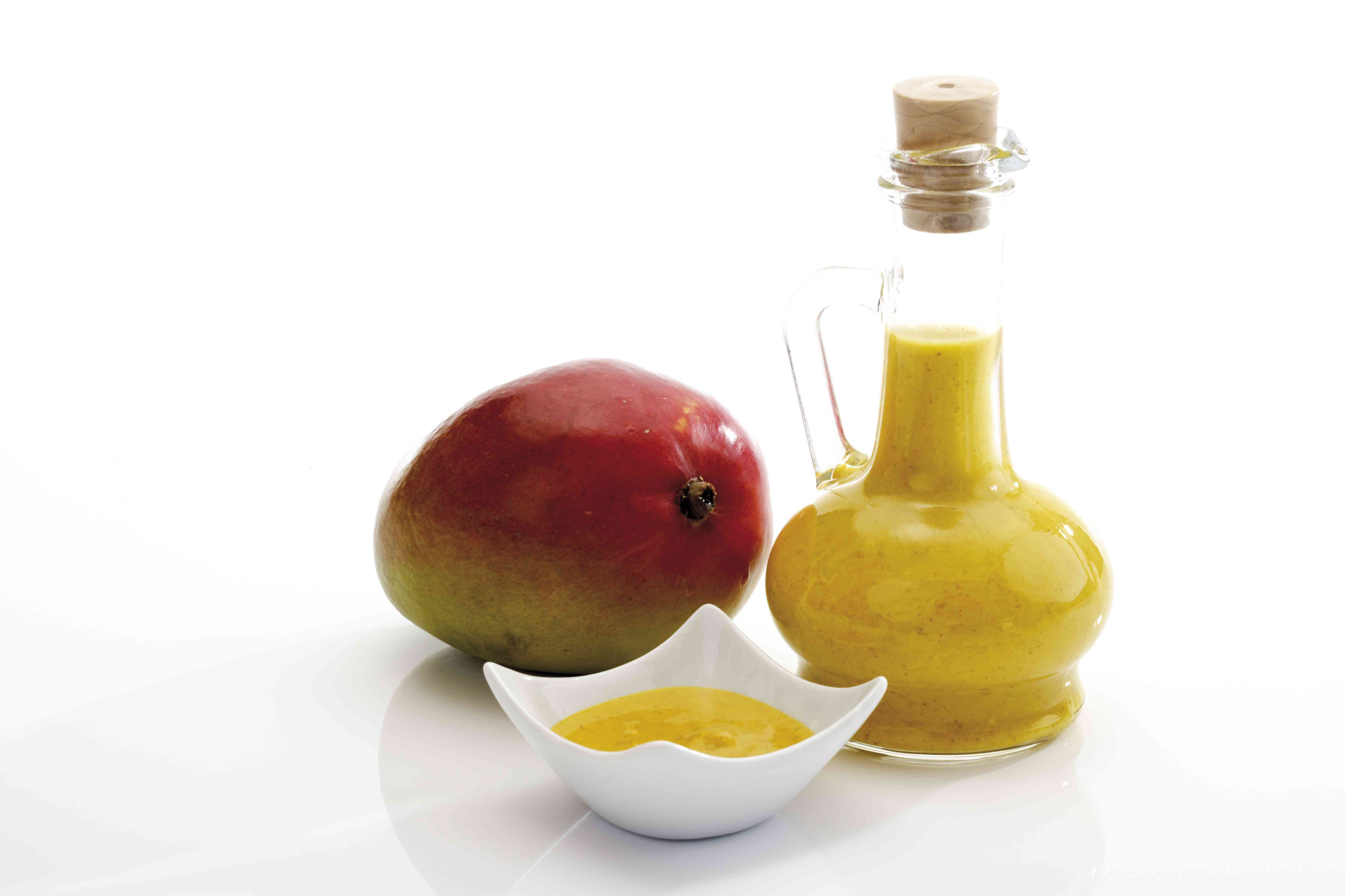 Mango sauce in a bowl and bottle with a fresh mango on a white background.