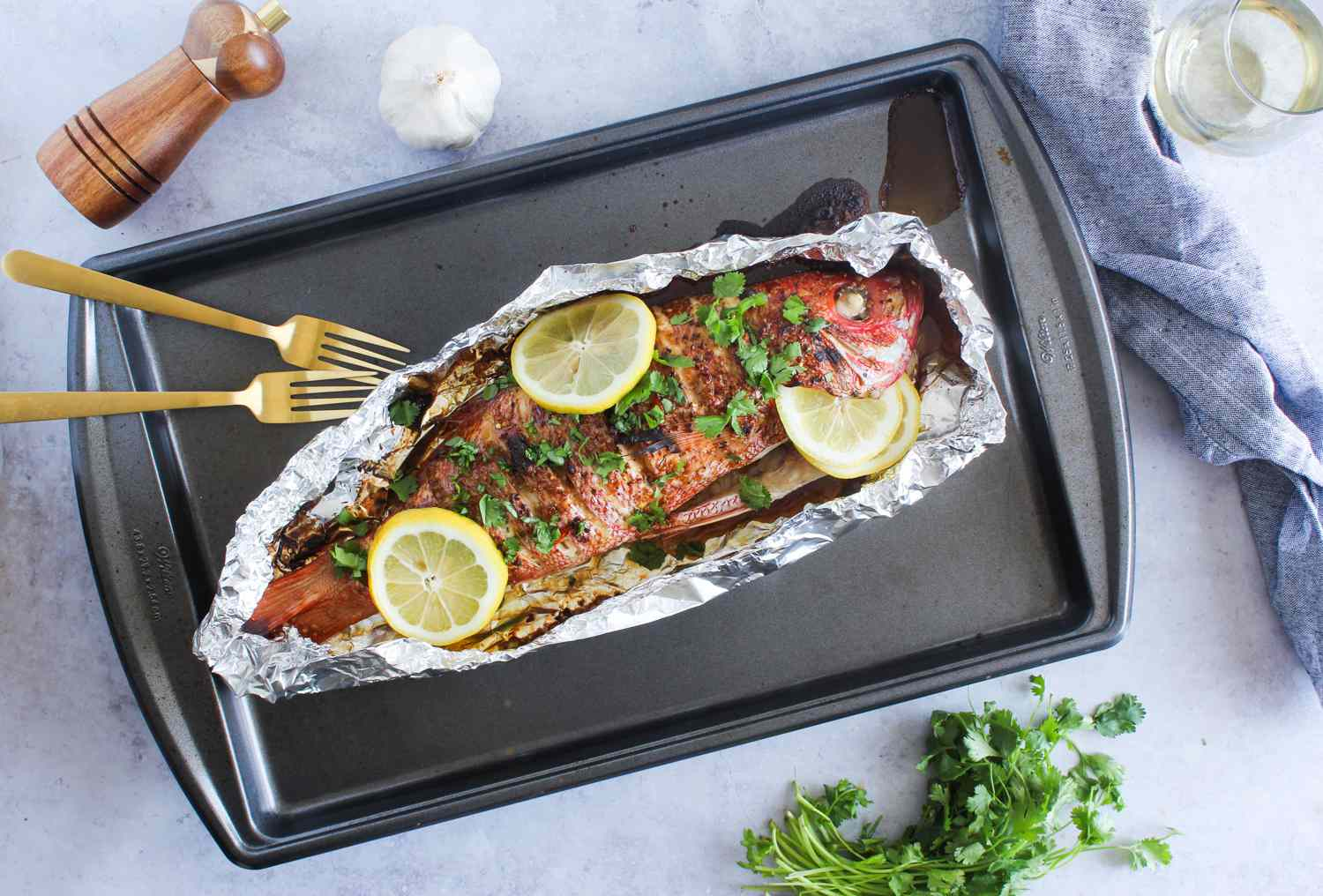 Cooked whole fish with lemon slices and coriander