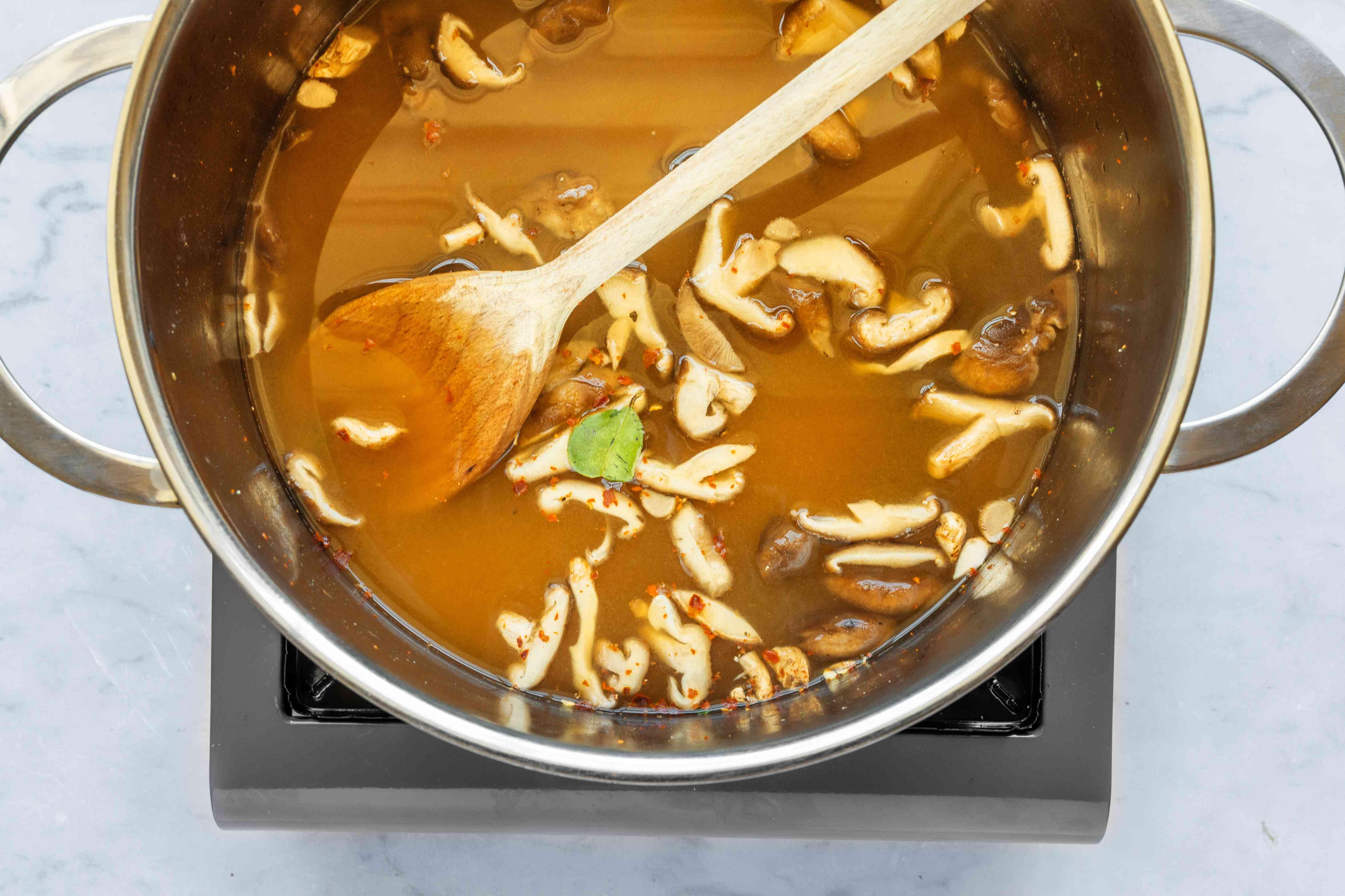 Add garlic, chili, lime leaves