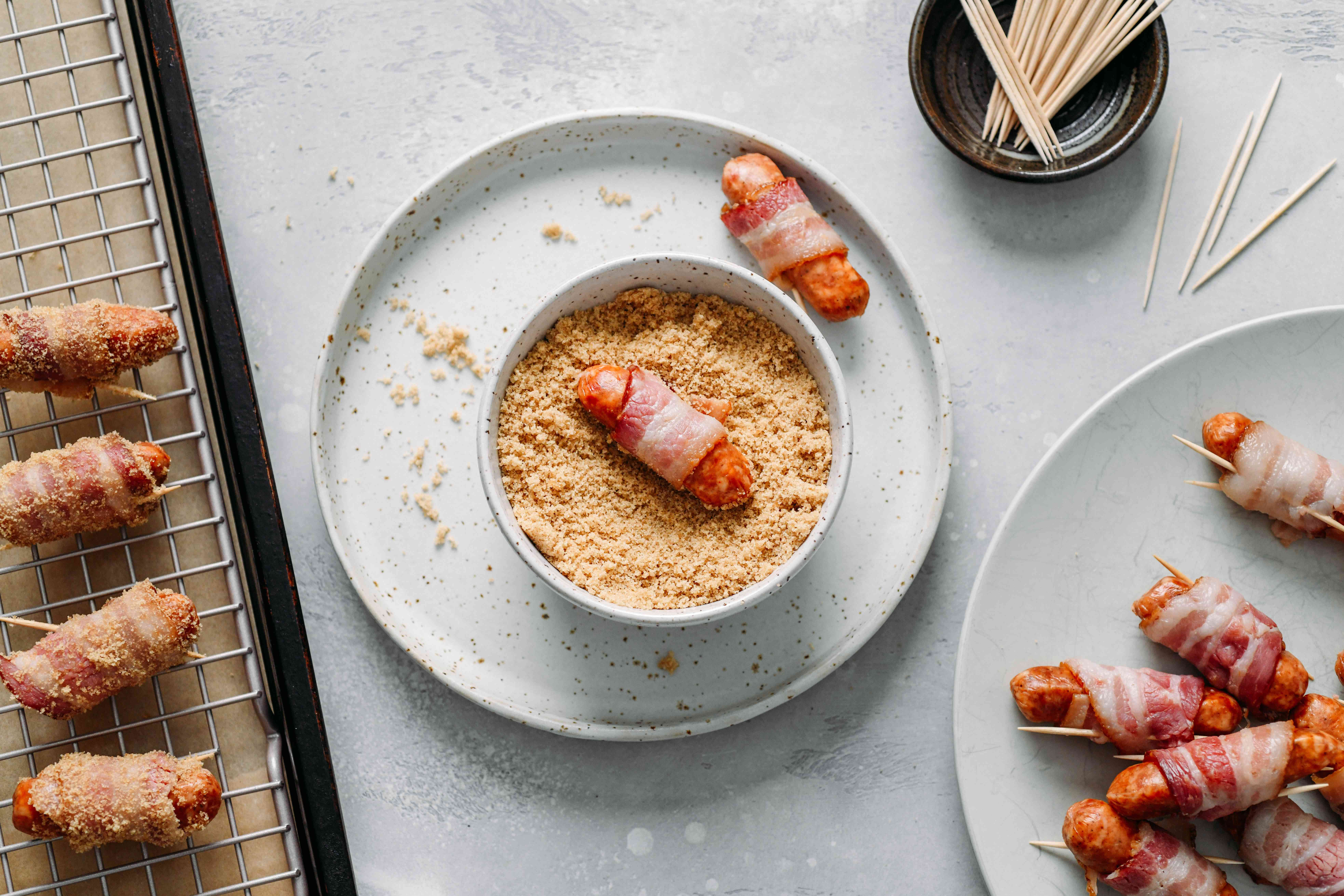 Place the sugar in a bowl and roll each little sausage and bacon bundle in i