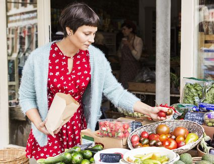 Woman selecting tomatoes at local farm shop