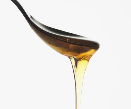 Close up of syrup dripping from spoon