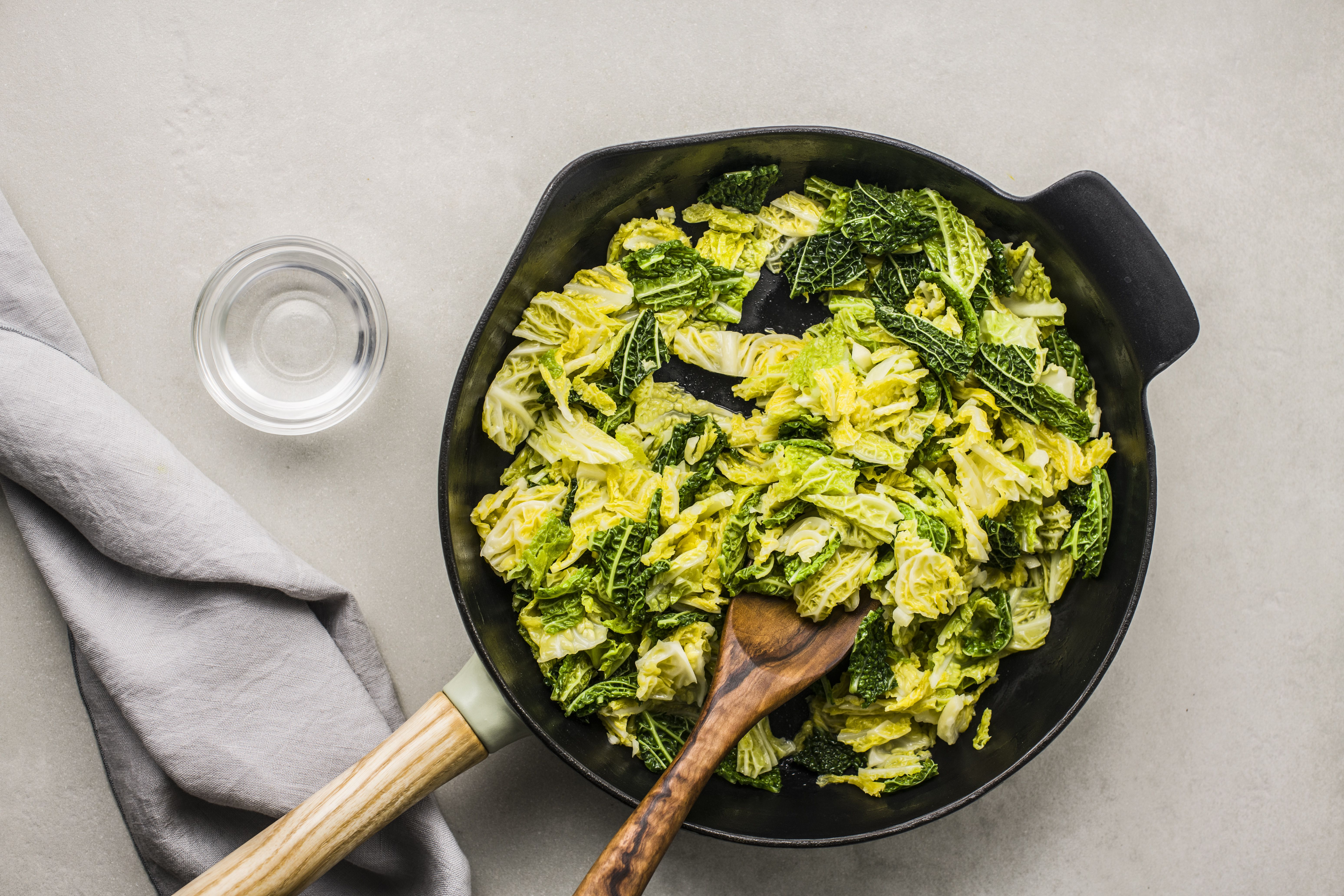 Adding water and stirring cabbage with a wooden spoon