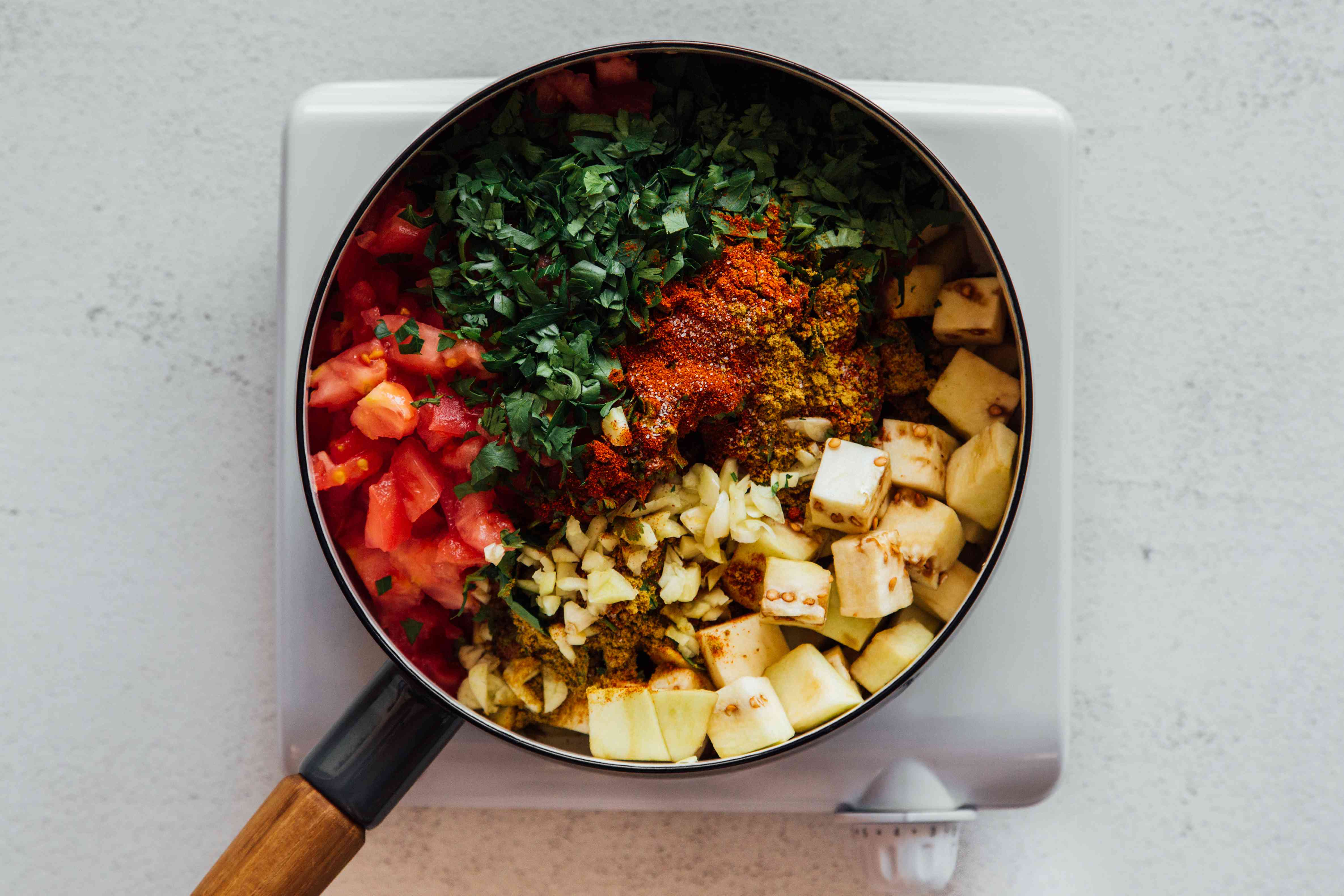 Eggplant, tomatoes, garlic, cilantro, parsley, paprika, cumin, salt, oil, water, and cayenne in a pan